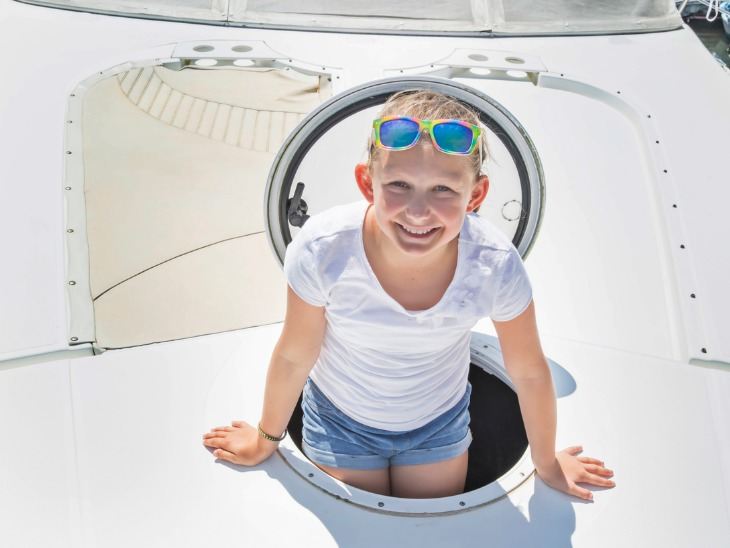 a young girl comes out of the deck hatch on a boat